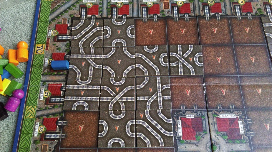Scoring example: train starting on the track highlighted by the blue token. Total points = 17. Starts on tile in ront of the token, then turns down and out throuh starting tile again up the board, then loops again and up to eventually turn around and down, finishin in the tile right next to the blue token (no. 27).